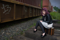 Sad runaway teen girl waits for train to escape her problem. Teen girl with purple dyed hair sits beside railway tracks as train goes by Royalty Free Stock Images