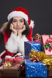 Sad Santa girl. Portrait of a sad Santa girl with Christmas gift boxes in front Royalty Free Stock Images