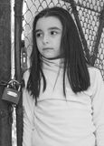 Sad and scared little girl. In front of a wire fence stock photography