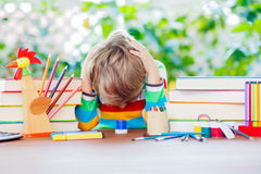 Sad school kid boy with glasses and student stuff Royalty Free Stock Photos