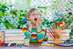Sad school kid boy with glasses and student stuff Royalty Free Stock Image