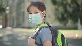 Sad schoolboy with backpack in face mask turning to camera. Portrait of upset Caucasian boy standing on sunny schoolyard