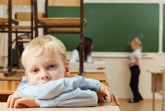 Sad schoolboy in classroom. Schoolboy is sitting in the half empty classroom after classes. He is bored Stock Image