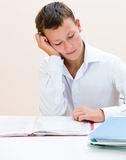 Sad schoolboy at the desk. Sad schoolboy at a Desk with notebooks Royalty Free Stock Photos