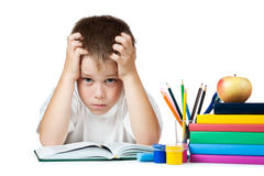 Sad schoolboy is doing his homework Stock Photos