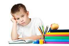 Sad schoolboy is doing his homework Stock Image
