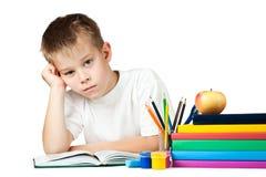 Sad schoolboy is doing his homework Stock Image
