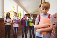 Sad schoolboy with friends in background at school corridor Stock Images