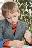 Sad schoolboy at a lesson Stock Images