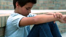 Sad schoolboy sitting alone in campus stock video