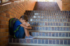 Sad schoolboy sitting alone on staircase. At school Stock Photos