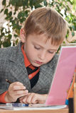 Sad schoolboy writing in a copybook Royalty Free Stock Photos