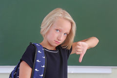 Sad schoolgirl with a backpack is showing a thumbs down in a classroom near green chalkboard. The child does not like the school. Stock Photos