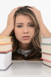Sad schoolgirl. Cheerful teenage schoolgirl holding her head in Stock Photography