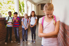 Sad schoolgirl with friends in background at school corridor Stock Image