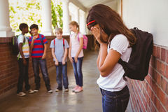 Sad schoolgirl with friends in background at school corridor Stock Photography