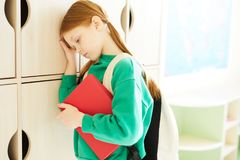 Schoolgirl being bullied. Sad schoolgirl with ponytails being bullied looking distraught, she holding book and leaning on wooden locker in classroom stock images