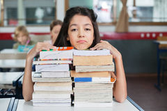 Sad Schoolgirl Resting Chin On Stacked Books At. Portrait of sad little schoolgirl resting chin on stacked books at desk in classroom Royalty Free Stock Images