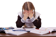 Sad schoolgirl sits at a school desk Royalty Free Stock Image
