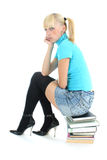 Sad schoolgirl sitting on stacked books Stock Images