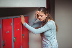 Sad schoolgirl standing in locker room Royalty Free Stock Photos