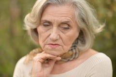 Sad senior beautiful woman. Portrait of sad senior beautiful woman in park Stock Image