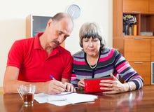 Sad senior couple calculating budget stock image