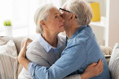 Sad senior couple hugging at home. Relationships, old age and people concept - sad senior couple hugging at home royalty free stock image