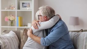 Sad senior couple hugging at home stock video footage