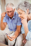 Sad senior couple looking at mobile phone Stock Images
