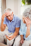 Sad senior couple looking at mobile phone Stock Photo