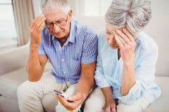 Sad senior couple looking at mobile phone royalty free stock photos