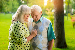 Sad senior couple outdoor. Man and women looking down. I'm always with you. Go through troubles together royalty free stock image