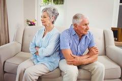 Sad senior couple sitting on sofa Royalty Free Stock Photography