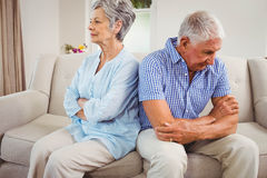 Sad senior couple sitting on sofa Stock Images