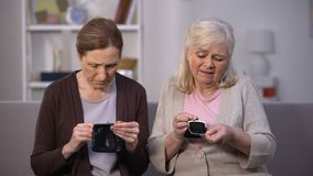 Sad senior female friends looking in empty wallets, poor budget, low incomes stock video
