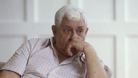 Sad senior grey haired man crying sit alone at home