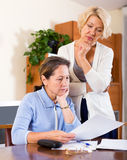 Sad senior ladies. Sad elderly ladies checking invoices at office.Focus on the left woman Royalty Free Stock Photos