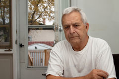 Sad Senior man. Sad looking senior caucasian man sitting indoors Stock Image