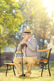 Sad senior man with a cane sitting on bench in a park Royalty Free Stock Images