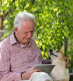 Old man with dog and tablet crying in garden. Sad senior man with his dog sitting on bench in garden, looking at tablet and crying stock photography
