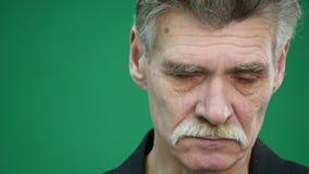 Sad senior man isolated on green background. Crying. Close up studio portrait.  stock footage