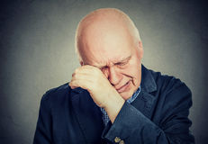 Sad senior man lonely grandfather, depressed crying. Isolated on gray background Royalty Free Stock Photography