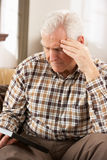 Sad Senior Man Looking At Photograph. In Frame Stock Image