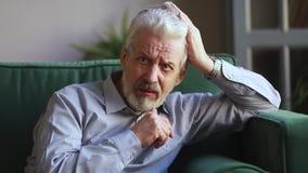 Sad senior man mourning grieving sitting alone at home. Sad senior grey haired man widower mourning grieving lost love sitting alone at home, upset desperate stock video footage