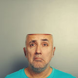 Sad senior man with open head. Over grey background Stock Images