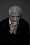 Sad senior man praying. Vertical view of sad senior man praying Stock Photo