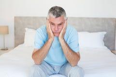 Sad senior man sitting on bed Stock Photo