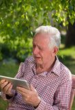 Old man with tablet crying in garden. Sad senior man sitting on bench in garden, looking at tablet and crying royalty free stock photo