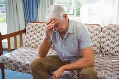 Sad senior man sitting on a couch Royalty Free Stock Photo